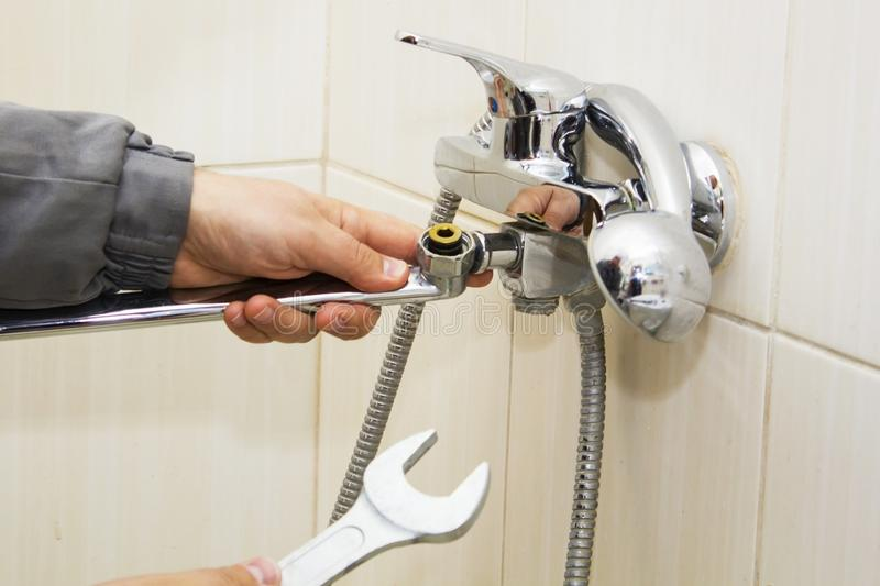 Plumber hands fixing water tap with spanner stock images