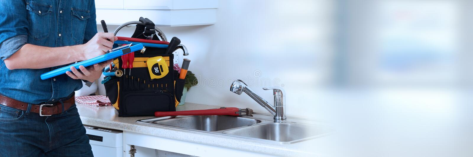 Plumber hands. Professional plumber working renovation in kitchen home stock image