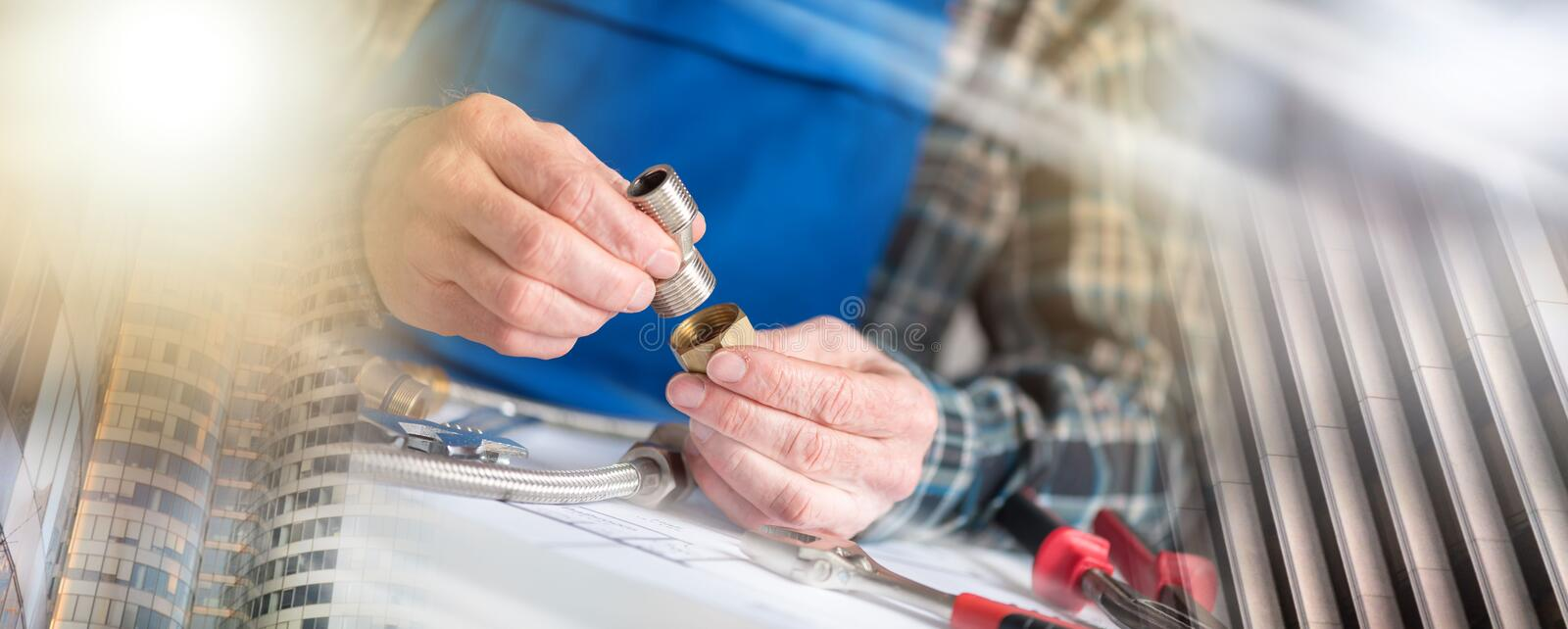 Plumber using plumbing fittings, light effect; multiple exposure royalty free stock images
