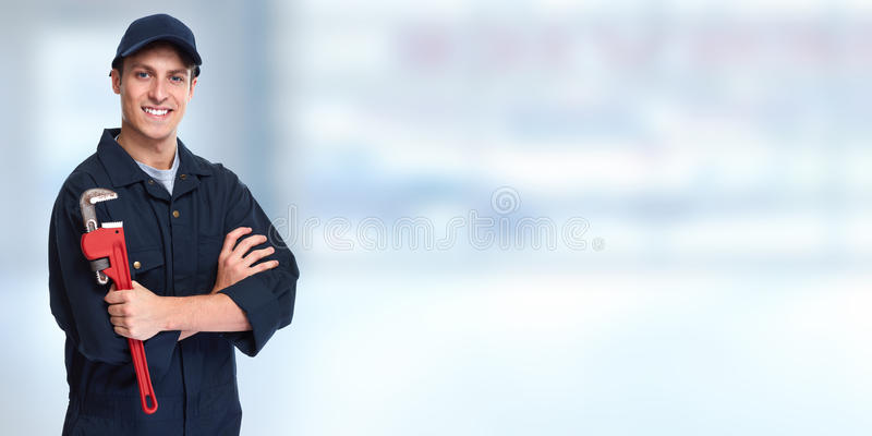 Plumber. Handsome plumber with wrench over blue background stock image