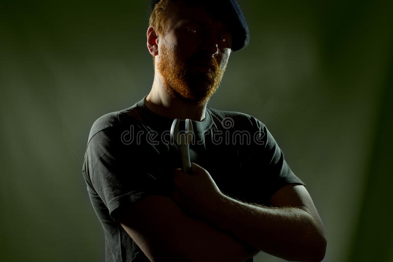 Plumber in hat with red beard in darkness. With glowing eyes stock photo