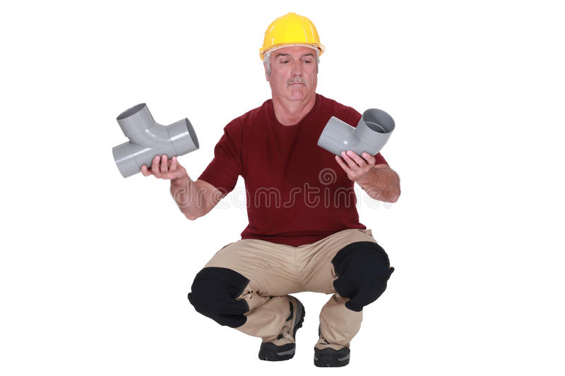 Plumber holding two pipes stock photo