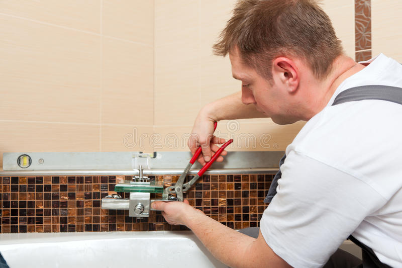 Download Plumber Installing A Mixer Tap In A Bathroom Stock Image - Image: 20662451