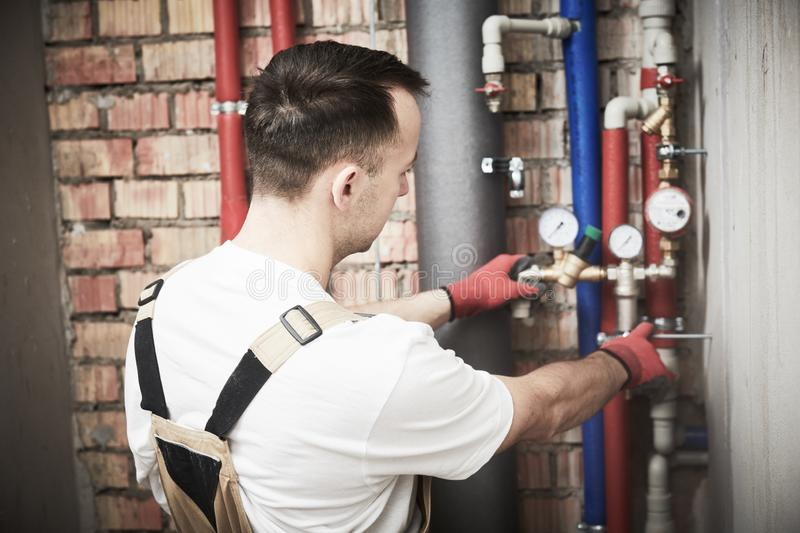 Plumber installing and mounting water equipment - meter, filter and pressure reducer royalty free stock photo