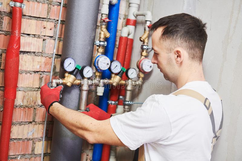 Plumber installing and mounting water equipment - meter, filter and pressure reducer stock photo