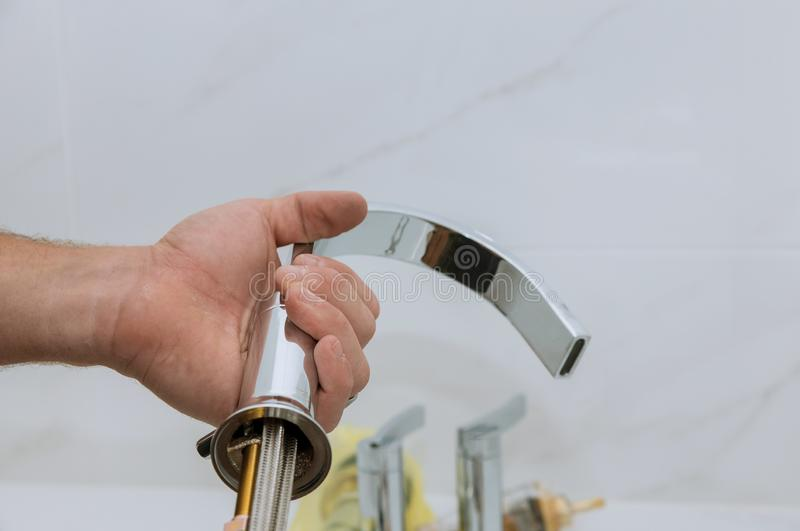 Plumber installing new mixer tap hands worker close up repair in bathroom at home royalty free stock photo