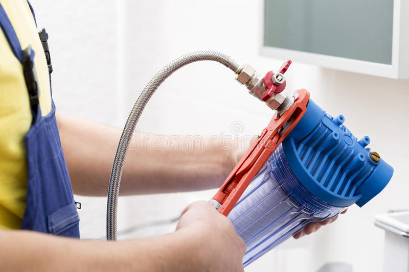 Plumber installing new water filter. In bathroom royalty free stock image