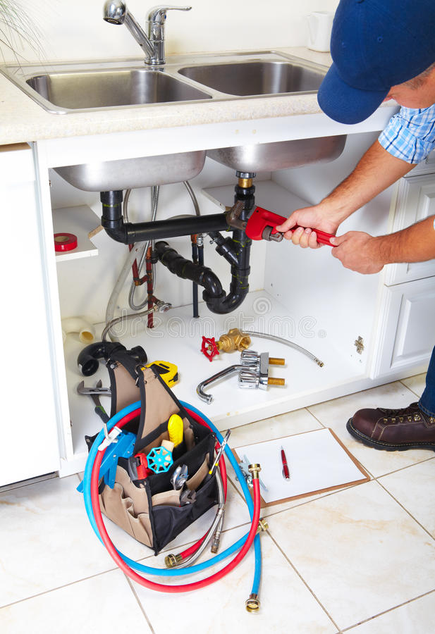 Plumber on the kitchen. royalty free stock image