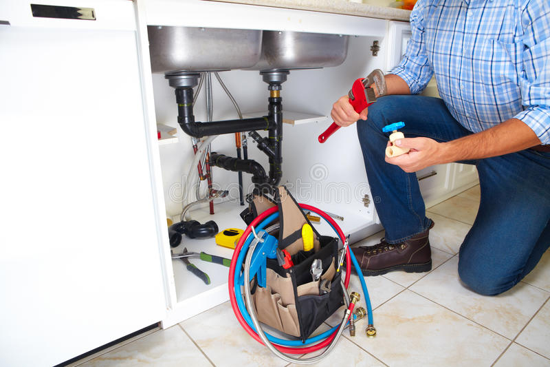 Plumber on the kitchen. royalty free stock photos
