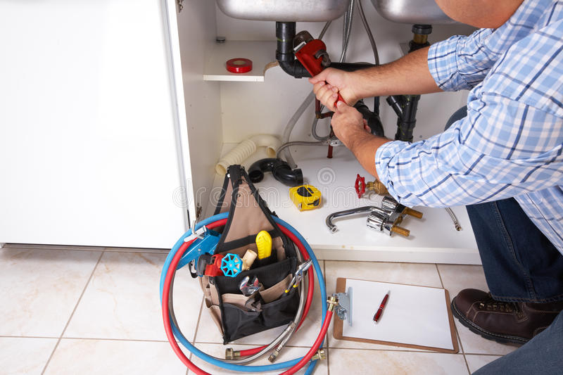 Plumber on the kitchen. stock photography