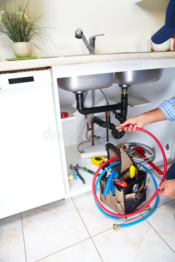 Plumber on the kitchen. stock photo