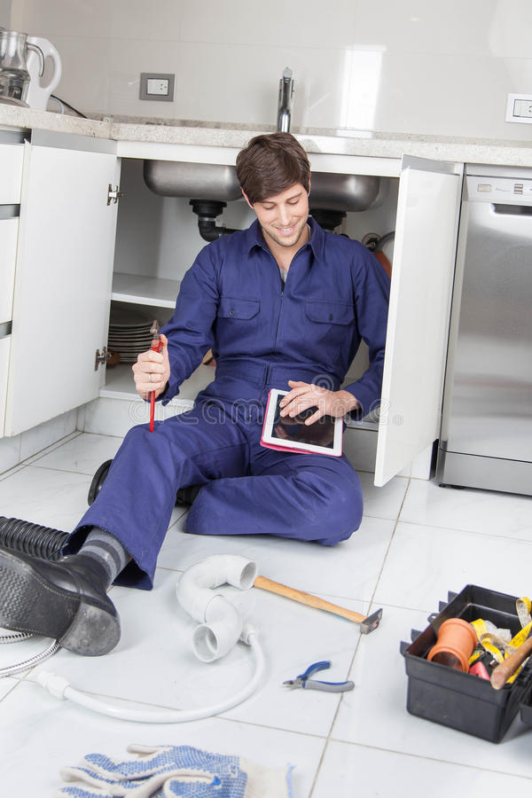 Plumber looking at the instructions in your tablet. Young plumber looking at the instructions in your tablet stock image