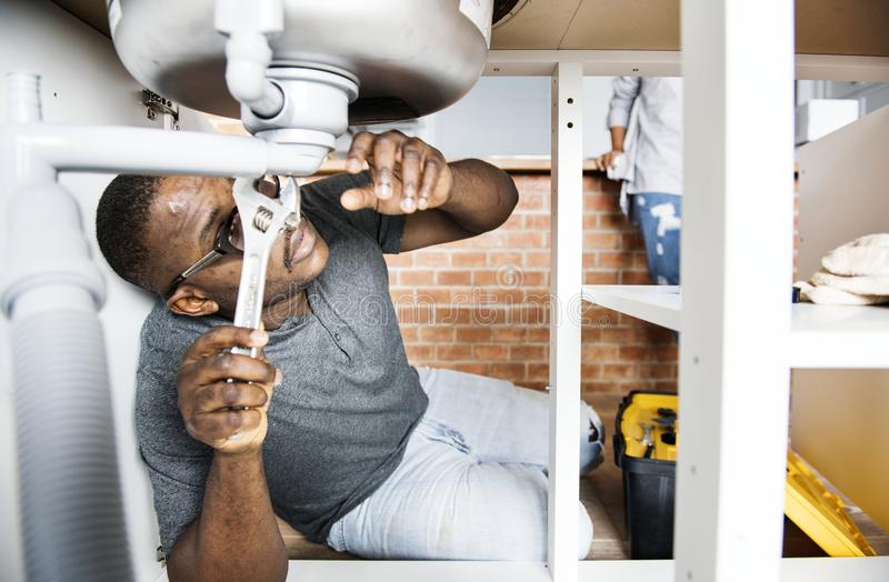 Plumber man fixing kitchen sink stock photo