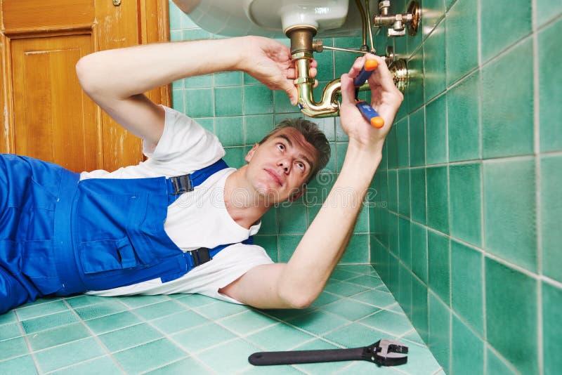 Plumber man repair leaky faucet tap. Plumber worker working with spanner during leaky faucet tap repair stock image