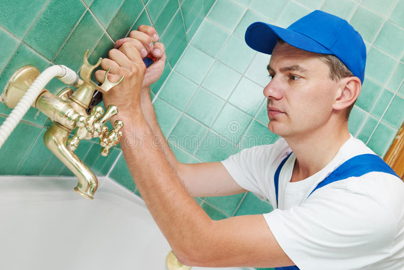 Plumber man repair leaky faucet tap. Plumber worker working with spanner during leaky faucet tap repair stock photography