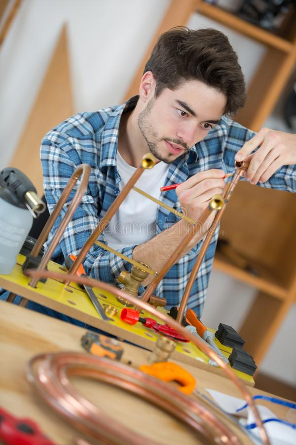 Plumber marking copper pipe royalty free stock image