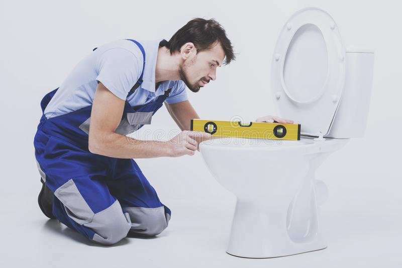 Plumber measures the toilet. royalty free stock image