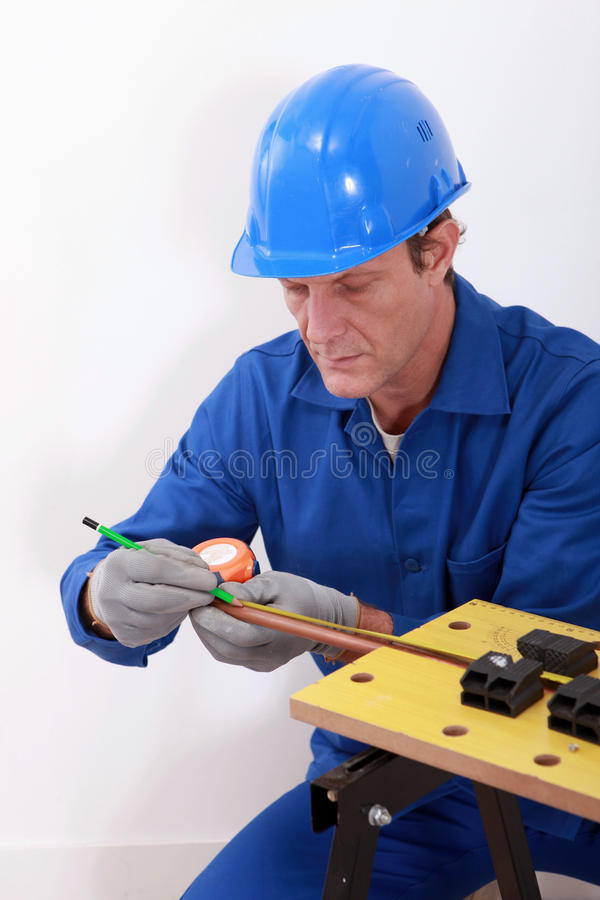 Plumber measuring copper pipe royalty free stock images