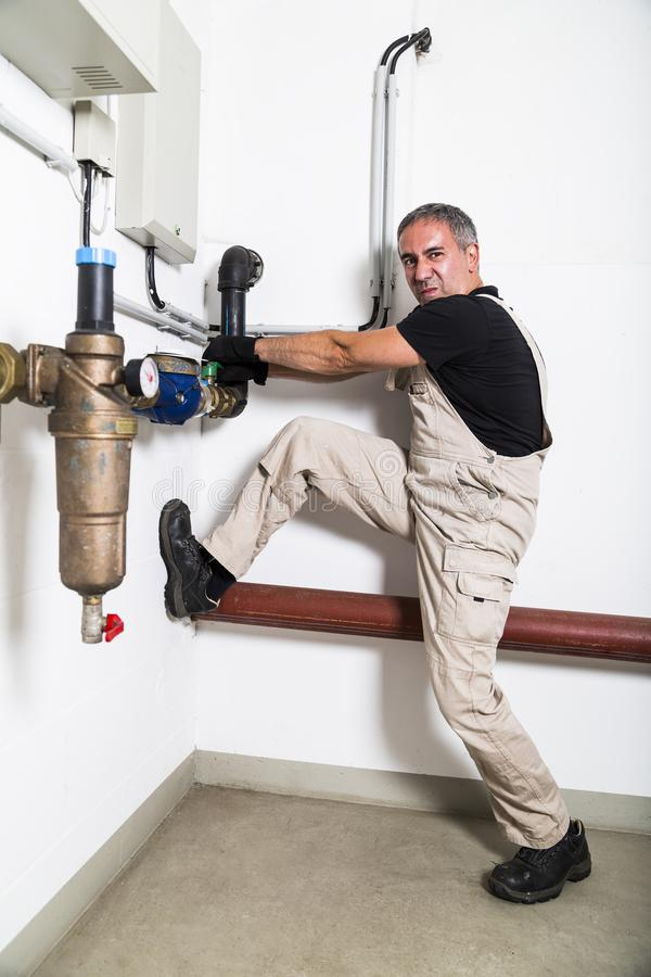 Plumber near water pipes opening water tap royalty free stock image