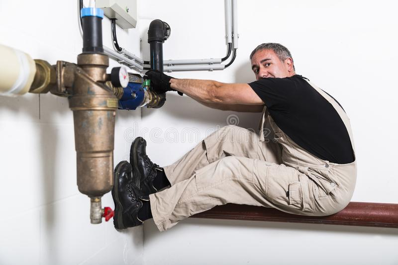 Plumber near water pipes opening water tap royalty free stock photos