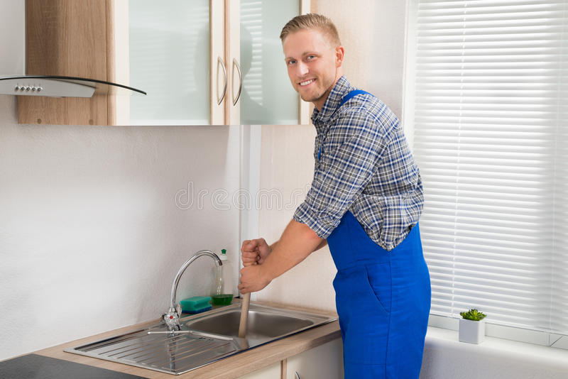 Plumber With Plunger In Kitchen. Young Happy Plumber Using Plunger In Kitchen Sink royalty free stock images