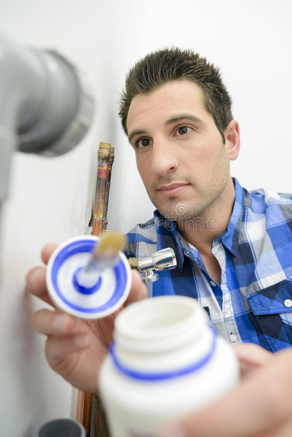 Plumber with pot glue. Plumber with a pot of glue royalty free stock images