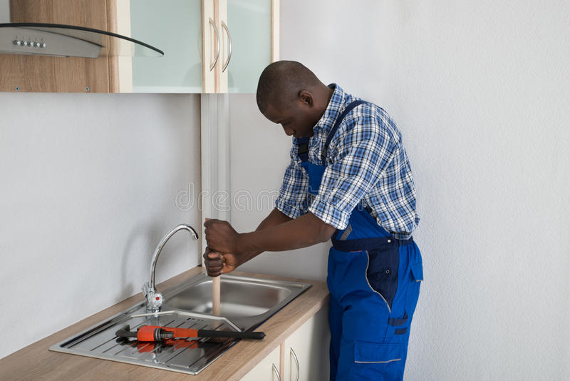 Plumber Pressing Plunger In Sink. Young Male African Plumber Pressing Plunger In Kitchen Sink royalty free stock photos