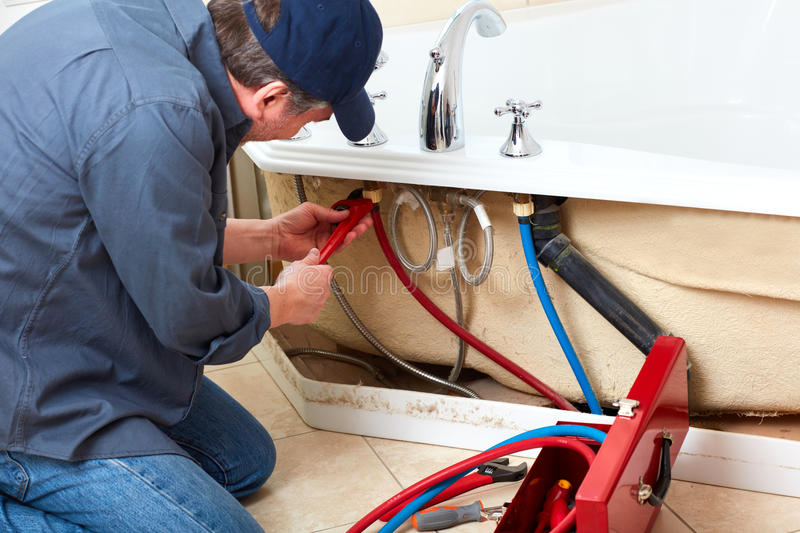 Plumber. Professional plumber doing renovation in bathroom home royalty free stock photography