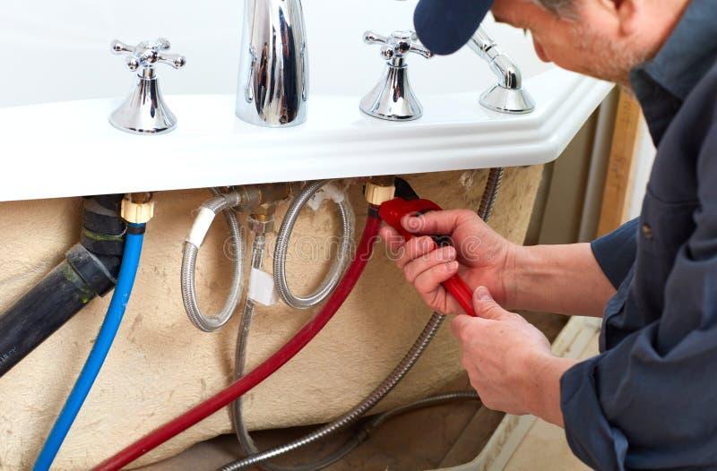 Plumber. Professional plumber doing renovation in bathroom home stock photos
