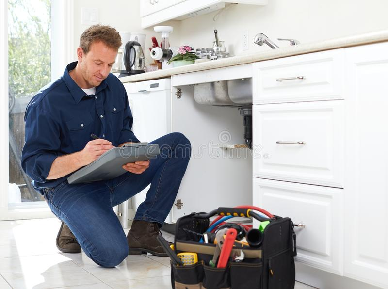 Plumber. Professional plumber doing renovation in kitchen home royalty free stock image