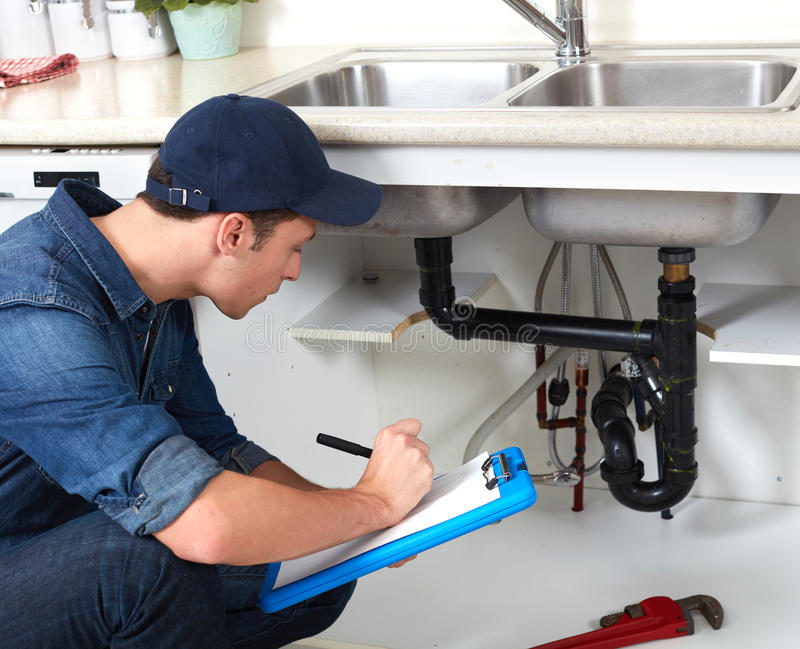 Plumber. Professional plumber doing renovation in kitchen home stock photo