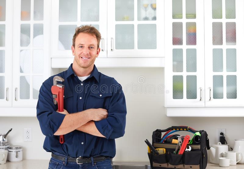 Plumber. Professional plumber doing renovation in kitchen home stock photography