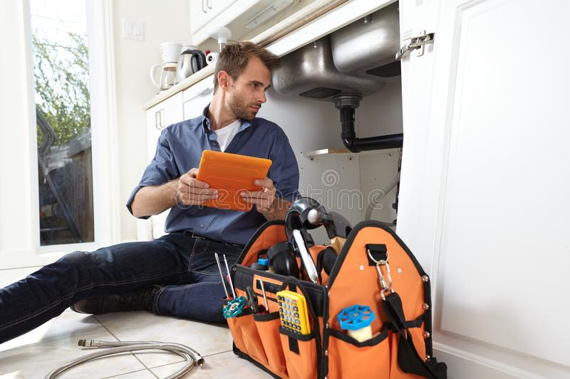 Plumber. Professional plumber doing renovation in kitchen home stock image