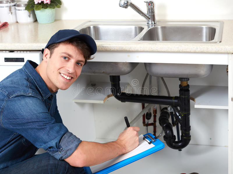 Plumber. Professional plumber doing renovation in kitchen home royalty free stock photo