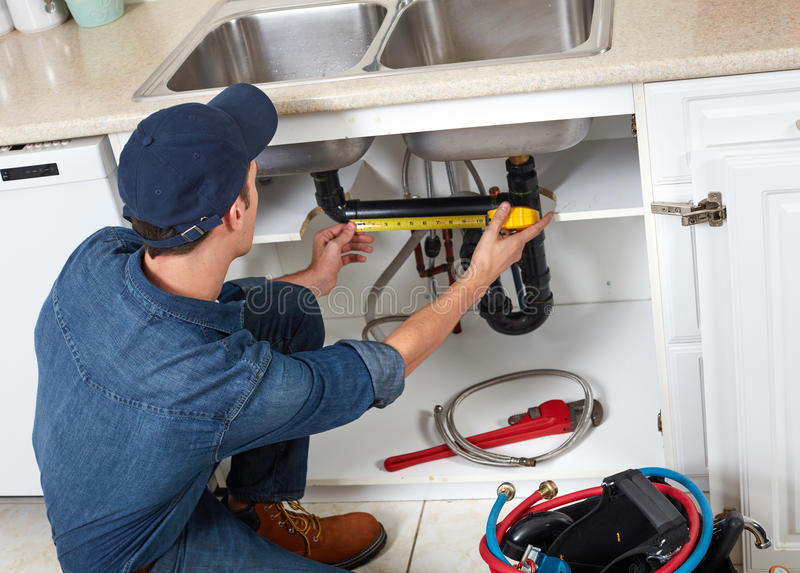 Plumber. Professional plumber doing renovation in kitchen home stock images