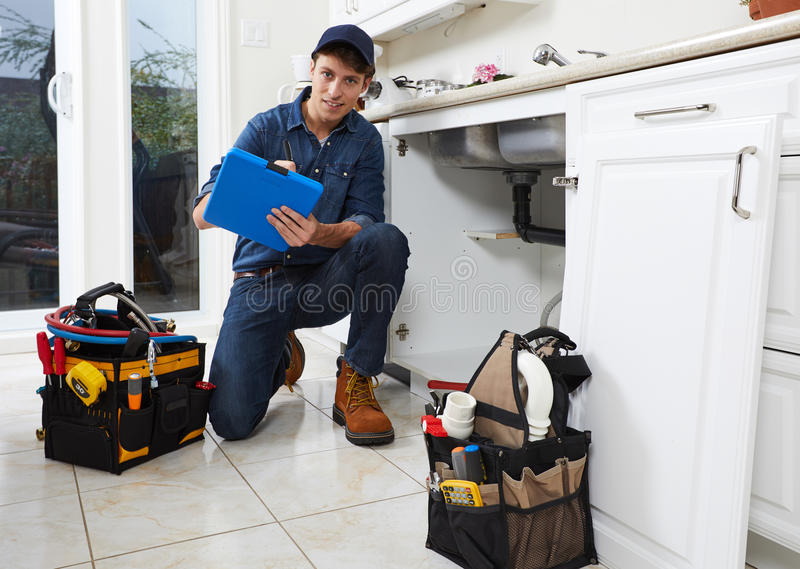 Plumber. Professional plumber doing renovation in kitchen home royalty free stock photos