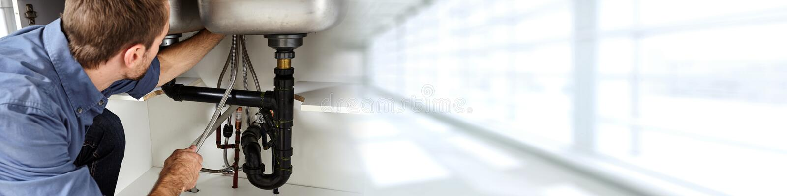 Plumber. Professional plumber doing renovation in kitchen home royalty free stock photography