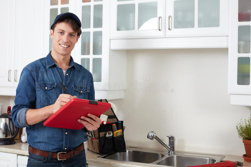 Plumber. Professional plumber doing reparation in kitchen home royalty free stock photography