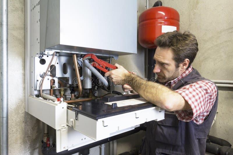 Plumber repairing a condensing boiler royalty free stock image