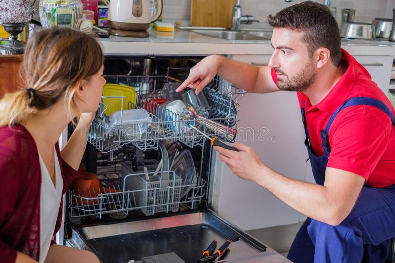 Plumber repairing and fixing dishwasher appliance home stock photo