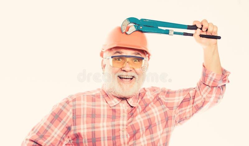 Plumber repairing or renovating. Home improvement. Plumber service. Man bearded plumber wear helmet and hold wrench tool stock image