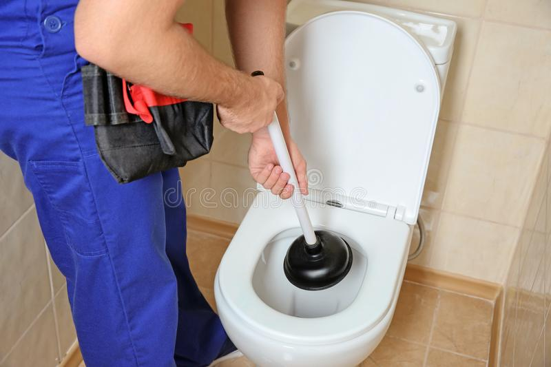 Plumber repairing toilet with hand plunger. Indoors stock images