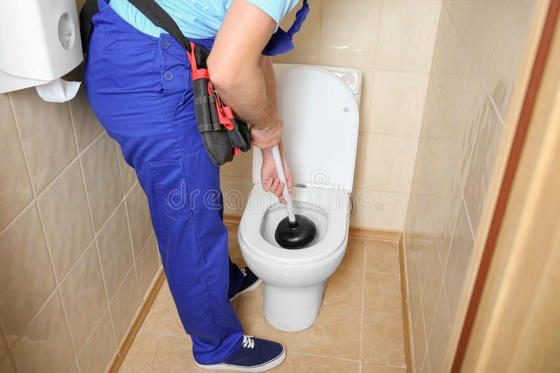 Plumber repairing toilet with hand plunger. Indoors royalty free stock photo