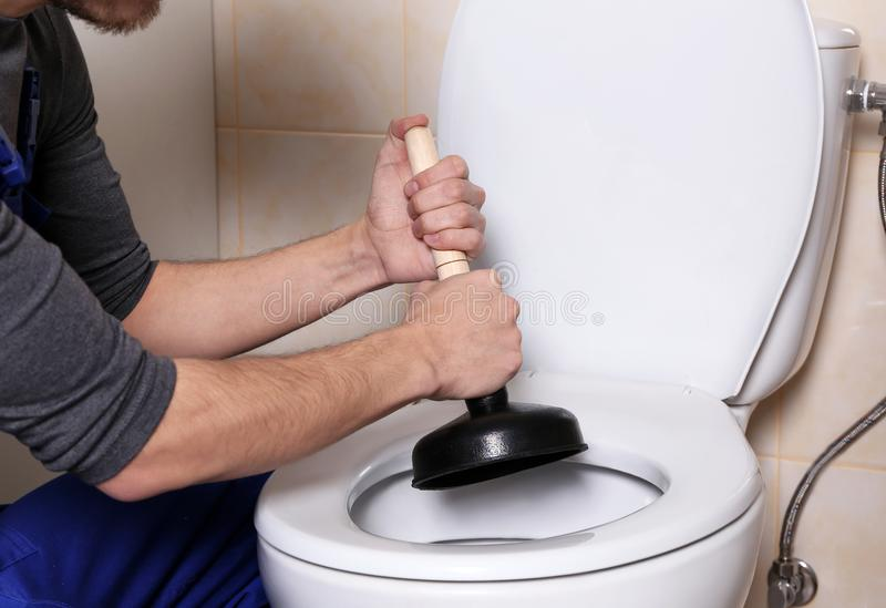 Plumber repairing toilet stock photo