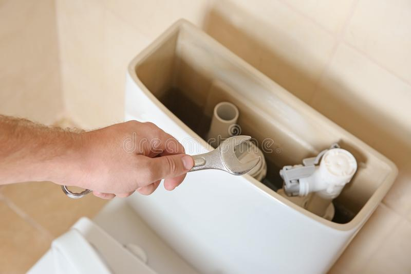 Plumber repairing toilet with wrench indoors, stock photo