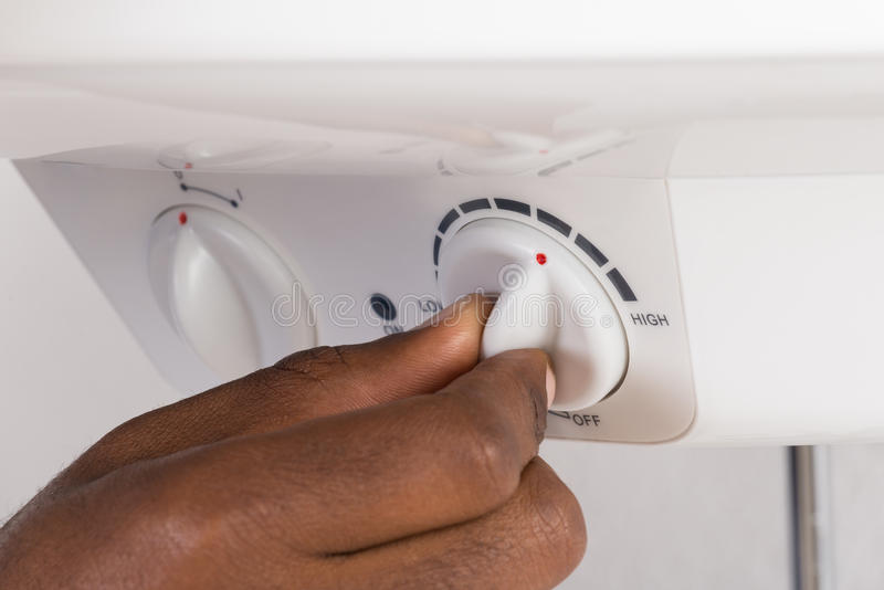 Plumber`s Hand Turning The Knob Of Electric Boiler stock images