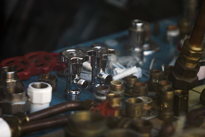 A plumber`s store`s screen window with tubs, joints, valves made of metals and plastics.. Close up of tubs, joints, valves made of metals and plastics at a stock images
