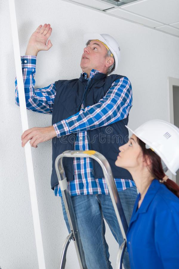 Plumber showing female trainee where to work stock images