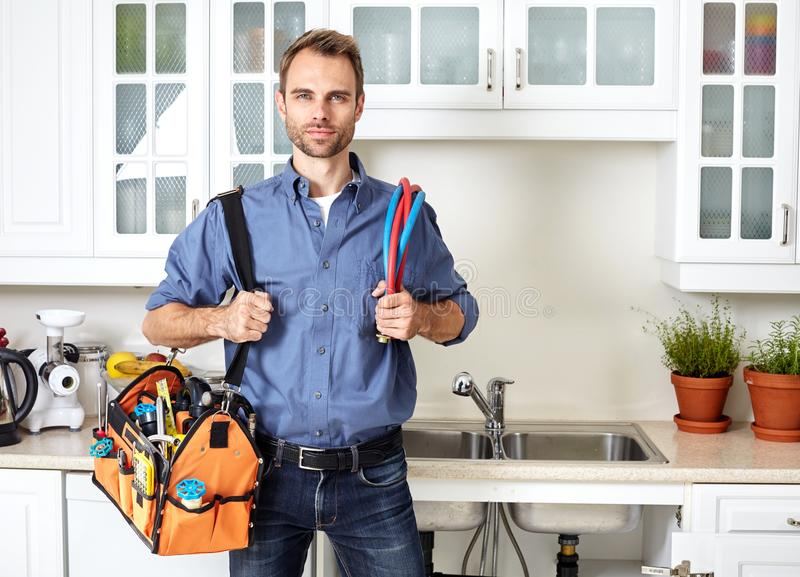 Plumber. Plumber with tools doing reparation in the kitchen royalty free stock photo