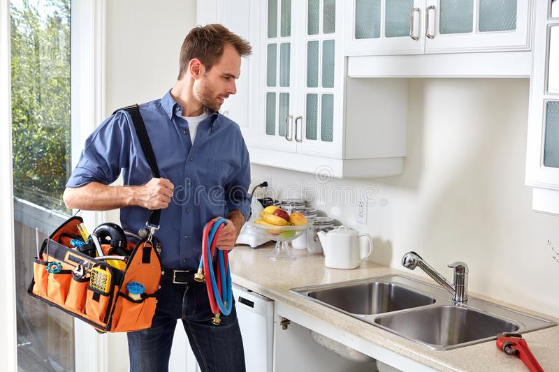 Plumber. Plumber with tools doing reparation in the kitchen royalty free stock images